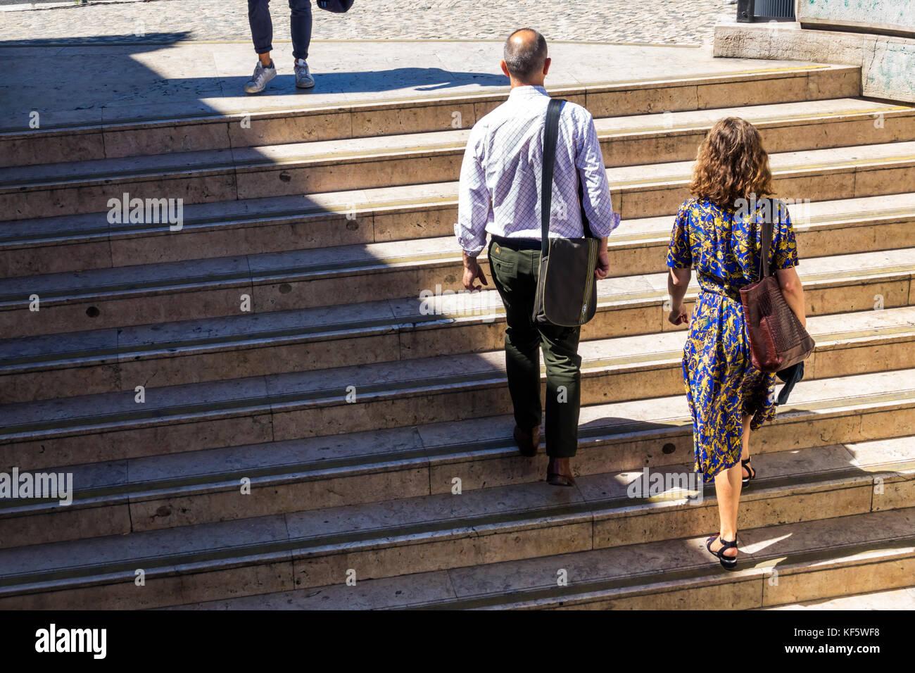 Lisbon Portugal Praca Marques de Pombal Metro Lisboa subway station stairs exterior man woman commuter ascending - Stock Image