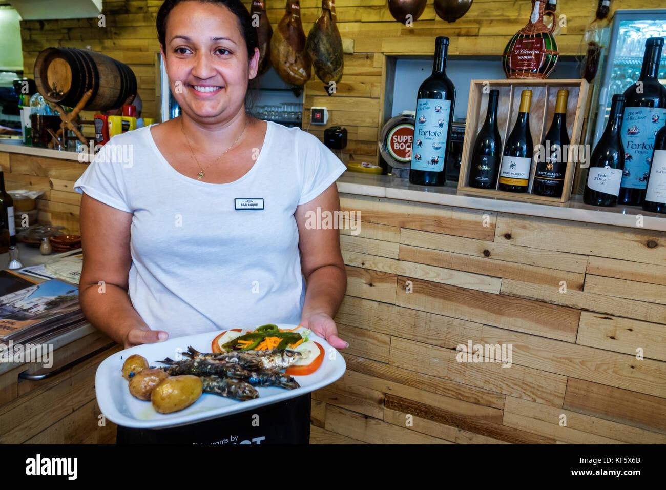 Lisbon Portugal Bairro Alto Restaurante Adega de Sao Roque restaurant dining Hispanic woman waitress carrying food - Stock Image