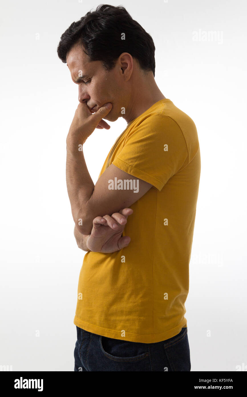 Thoughtful man is downcast. Looking down with his hand on his mouth. Sadness. Depression. He is wearing a yellow - Stock Image