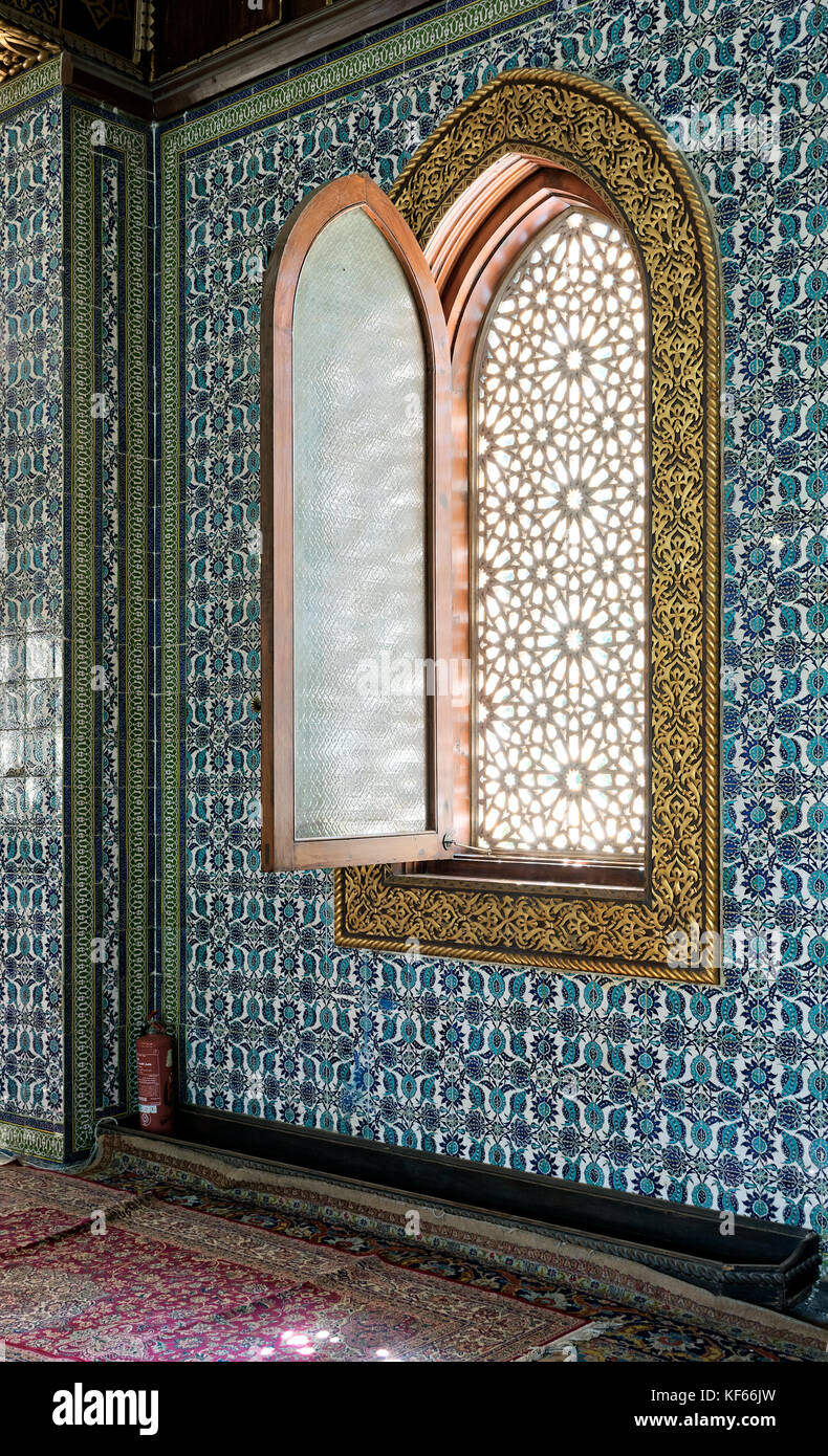 Wooden arched window framed by golden floral pattern ornaments over ceramic tiles wall with floral blue patterns - Stock Image
