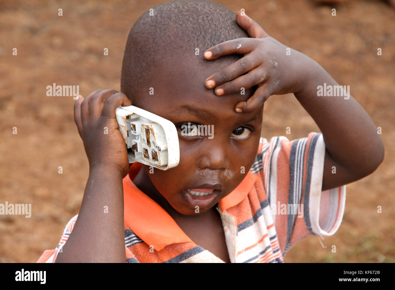 Living in the Kenya Slum Aerias - Young kid playing with broken phone - Stock Image