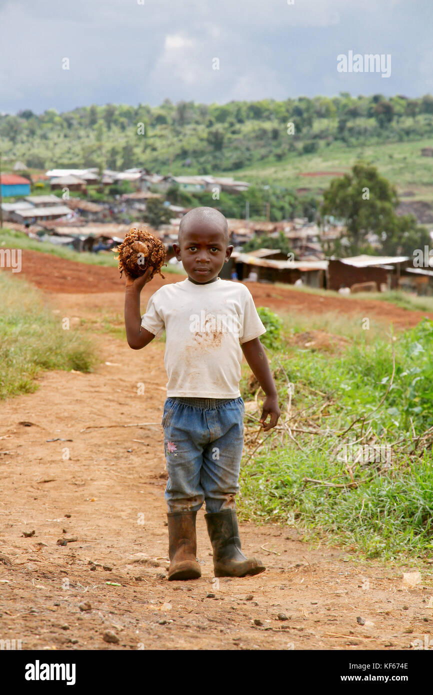 Living in the Kenya Slum Aerias - Young kid playing with a own made football - Stock Image