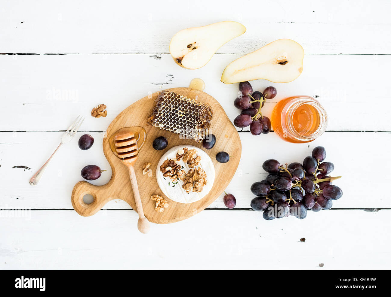 Camembert cheese with grape, walnuts, pear and honey - Stock Image