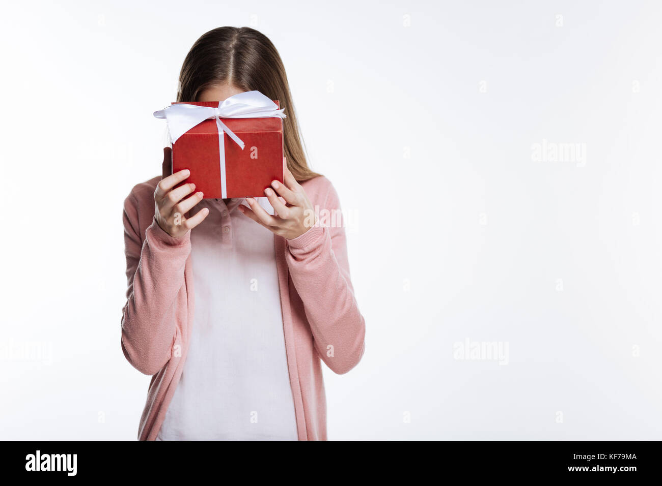 Shy girl hiding her face behind a gift box - Stock Image