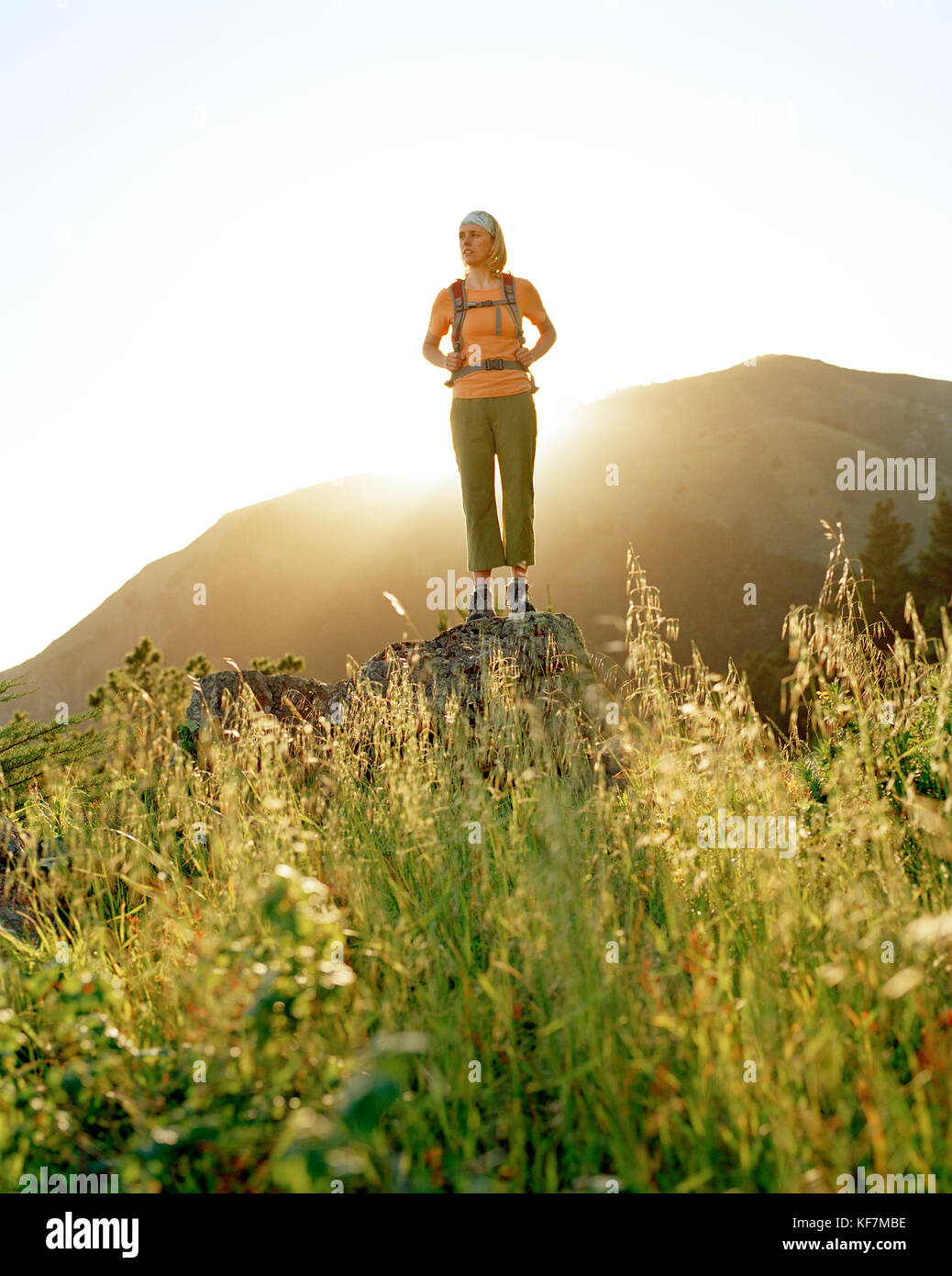 USA, California, Marin Headlands, young woman hiking and standing on a rock in front of Mount Tamalpais - Stock Image