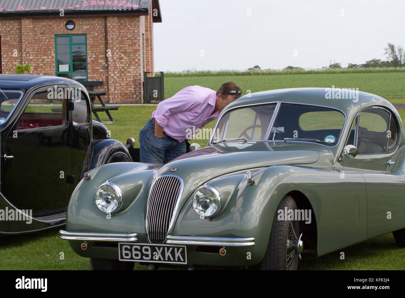 Man inspecting a classic green Jaguar XK coupe - Stock Image