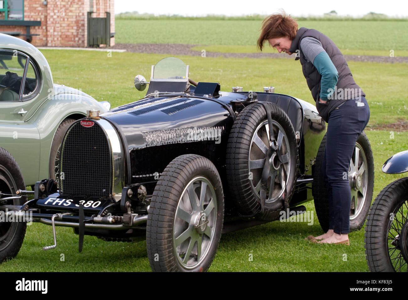 Woman inspecting a classic soft top Bugatti - Stock Image