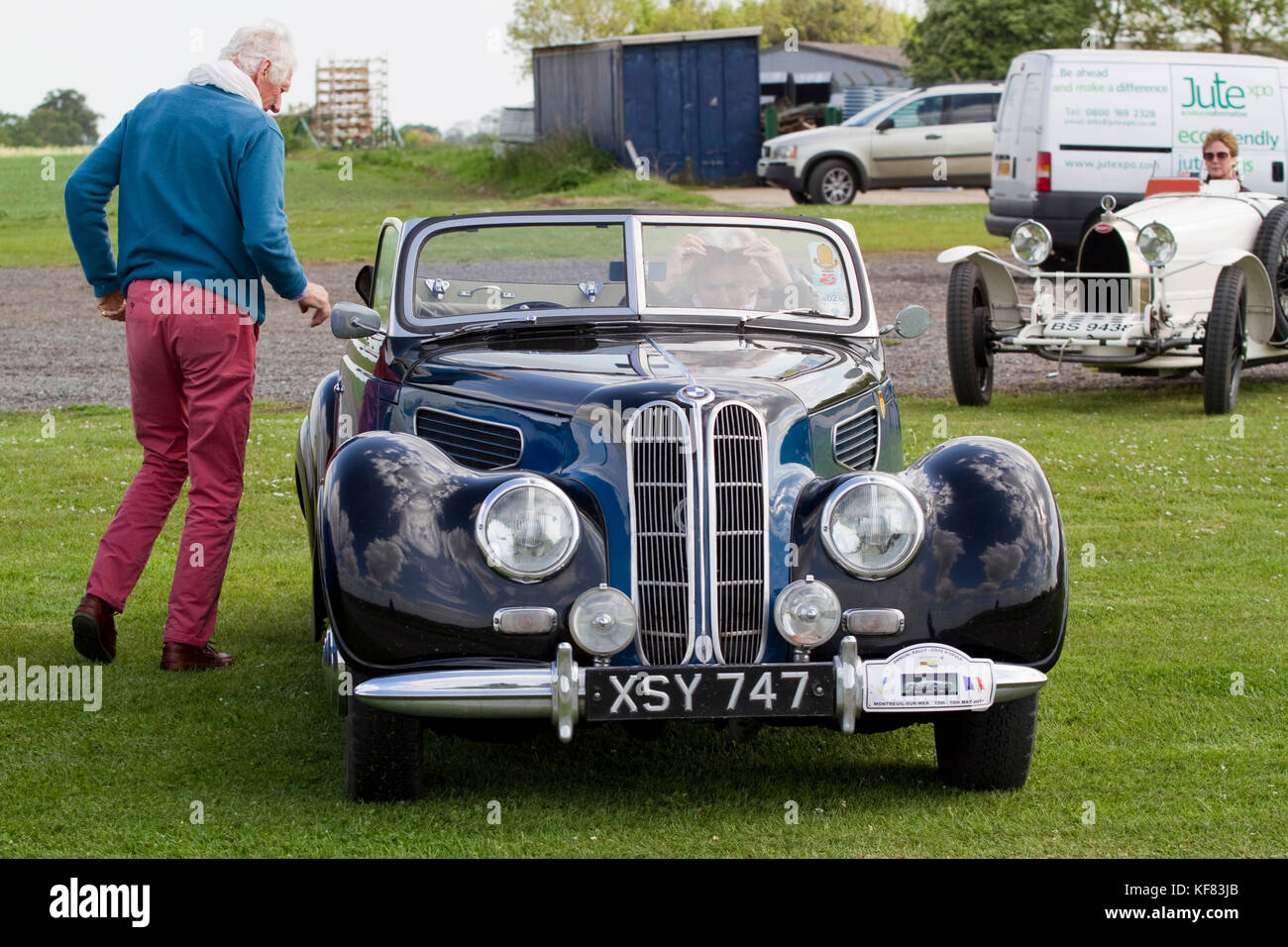 Man inspecting a classic soft top BMW - Stock Image