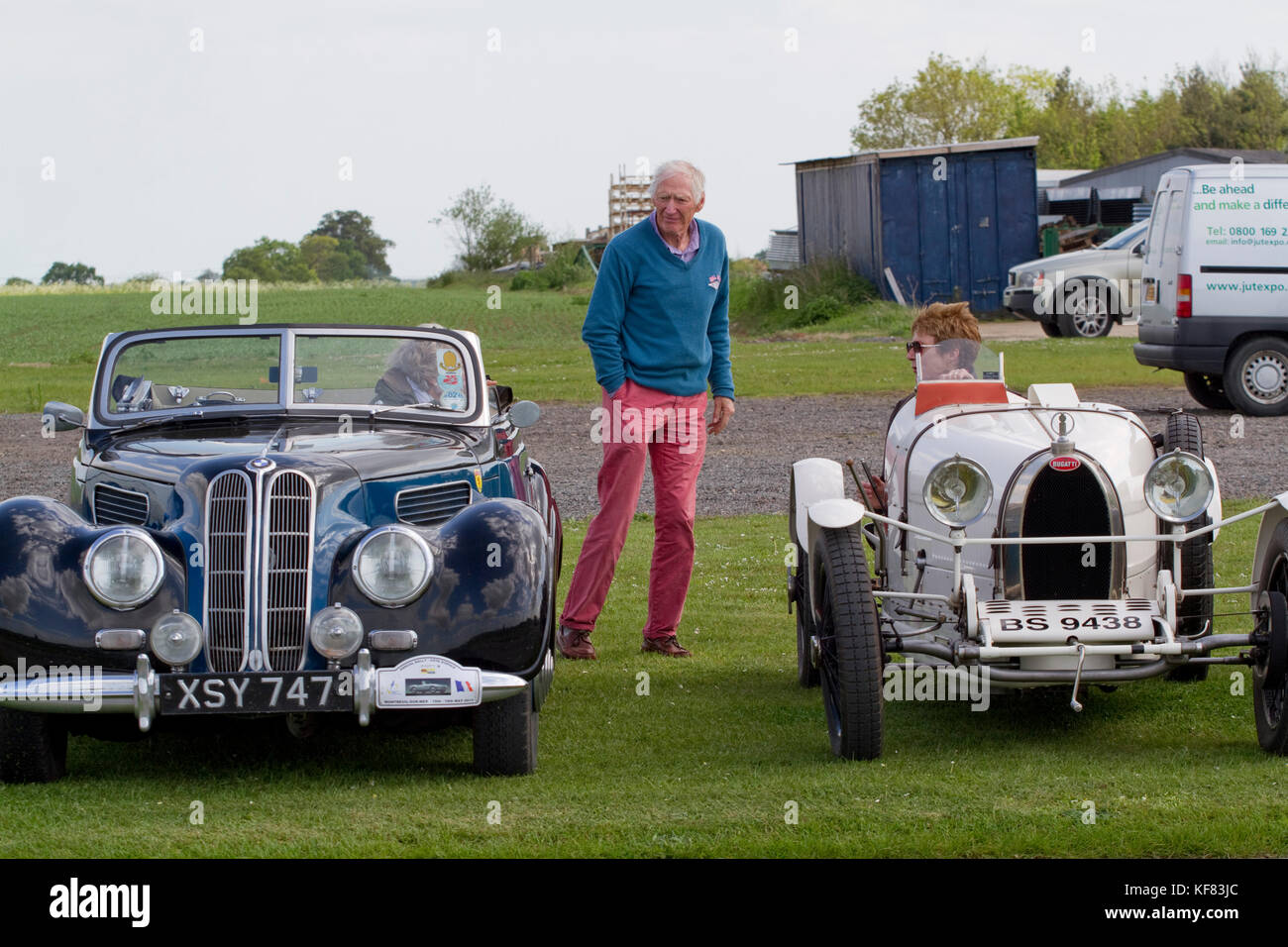 Man inspecting a classic soft top BMW and Bugatti - Stock Image