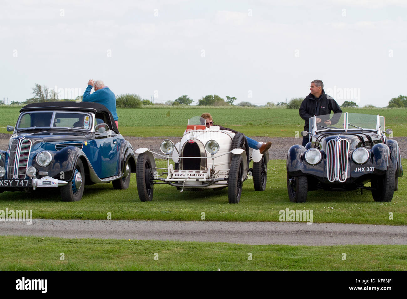 Drivers of two classic BMWs and a Bugatti meet on a club run - Stock Image