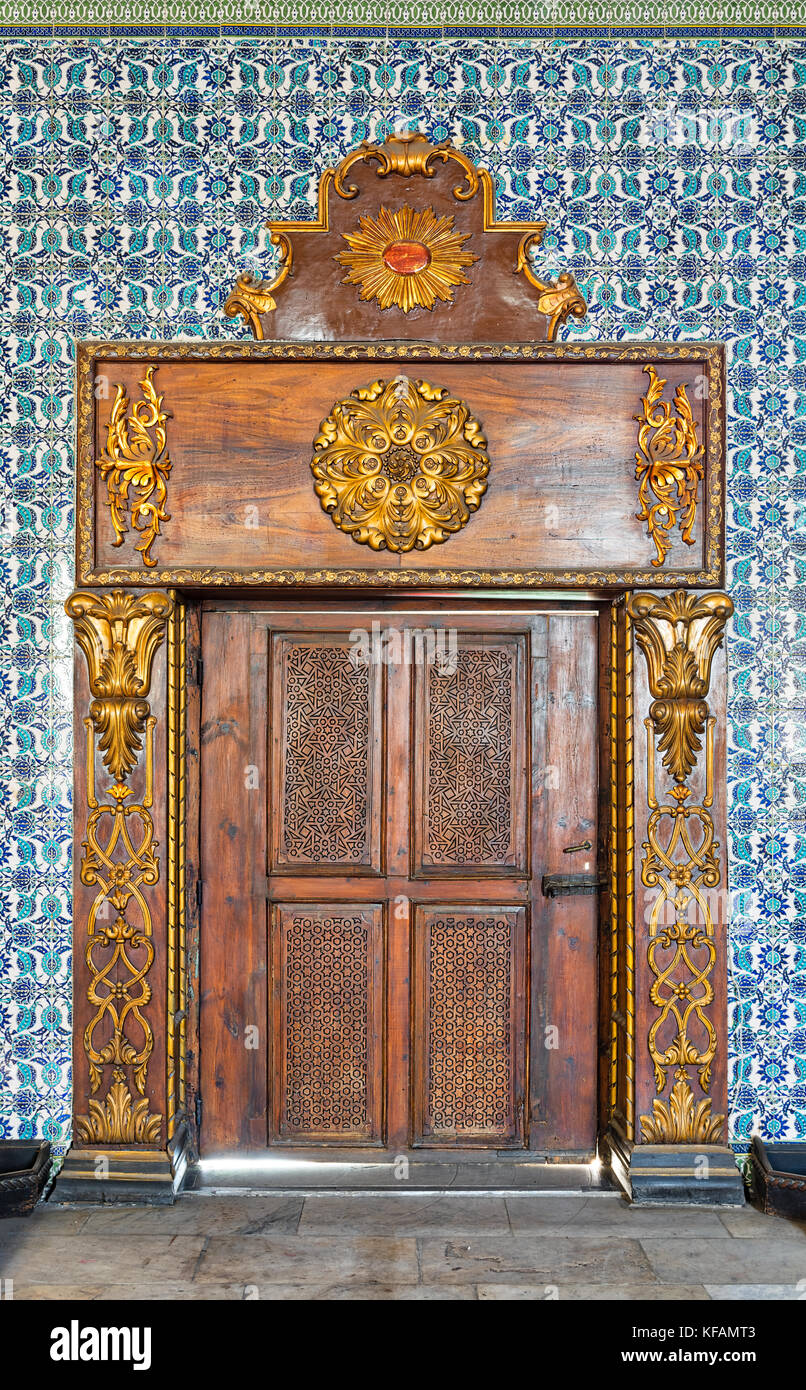 Closed wooden engraved aged door framed by golden ornate wooden frame on Turkish ceramic tiles wall with floral - Stock Image