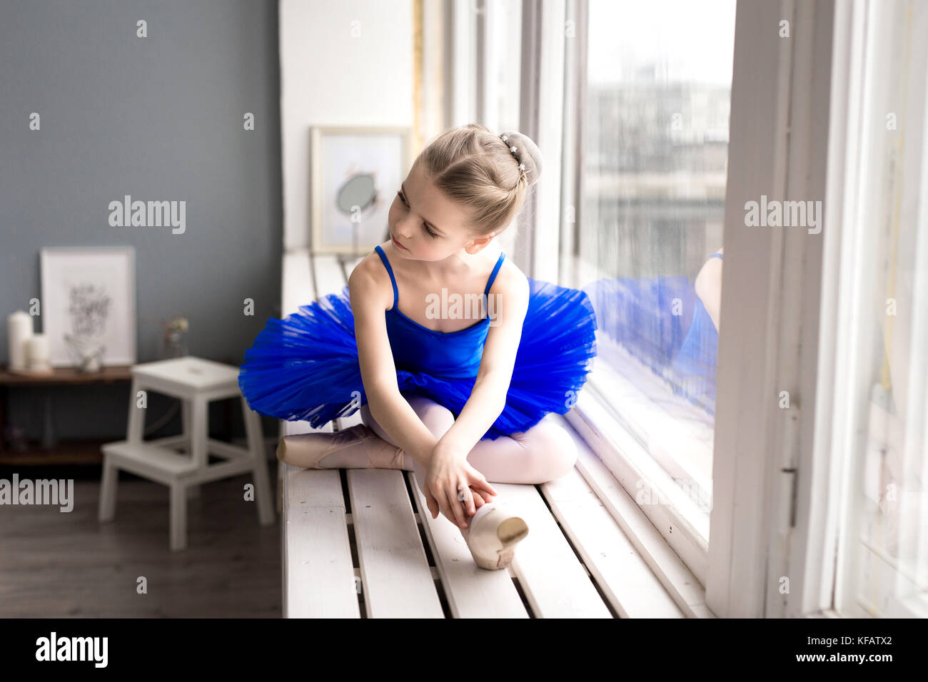 little girl dreams of becoming a ballerina. Child girl in a blue ballet costume dancing in a room. - Stock Image