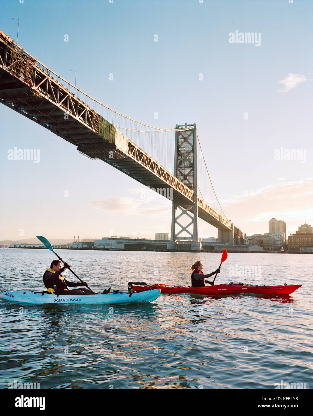 USA, California, San Francisco, a man and woman kayak in the San Francisco Bay under the Bay Bridge, the city of - Stock Image