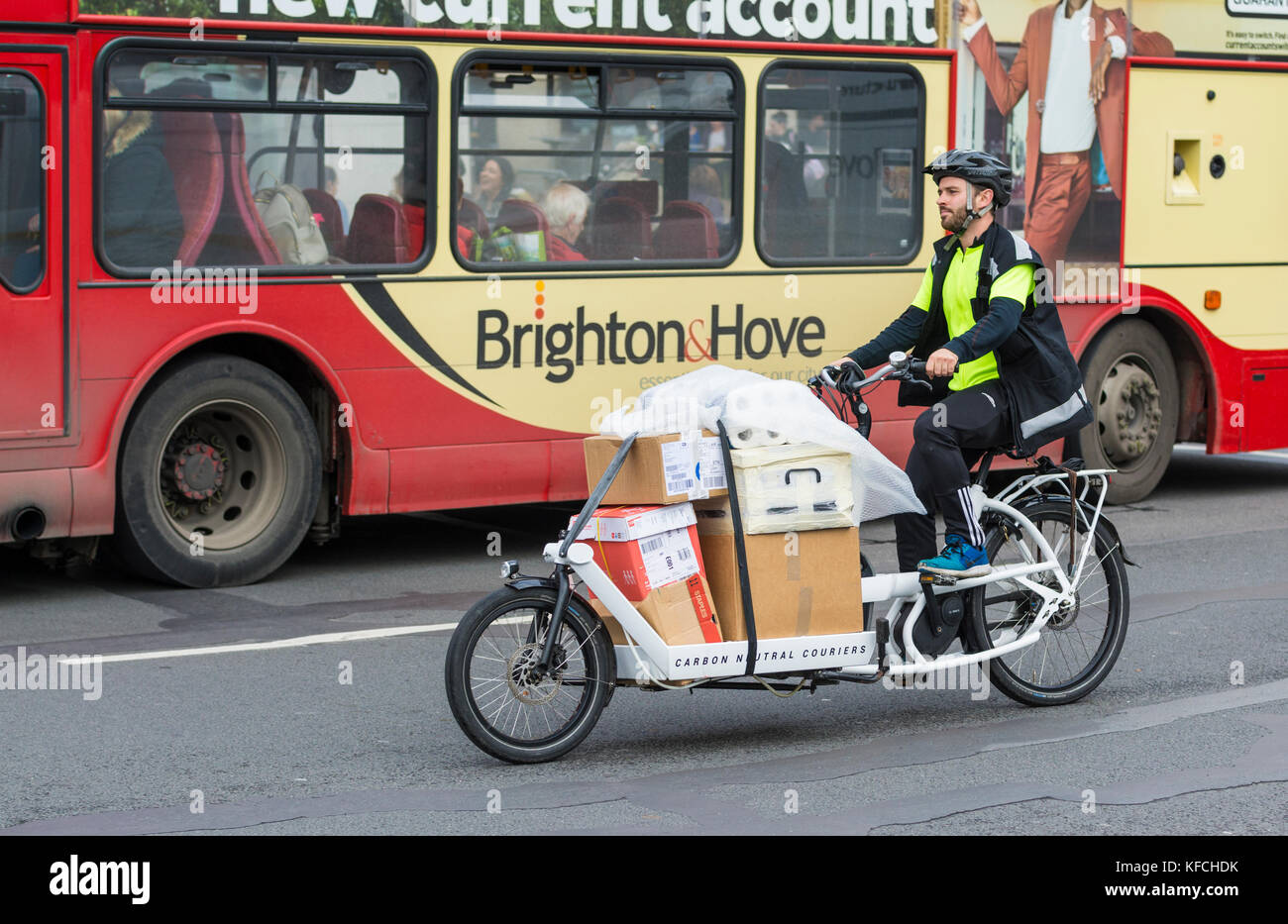 Cyclist on a pedal powered delivery vehicle working for Carbon Neutral Couriers, making deliveries in the city in - Stock Image