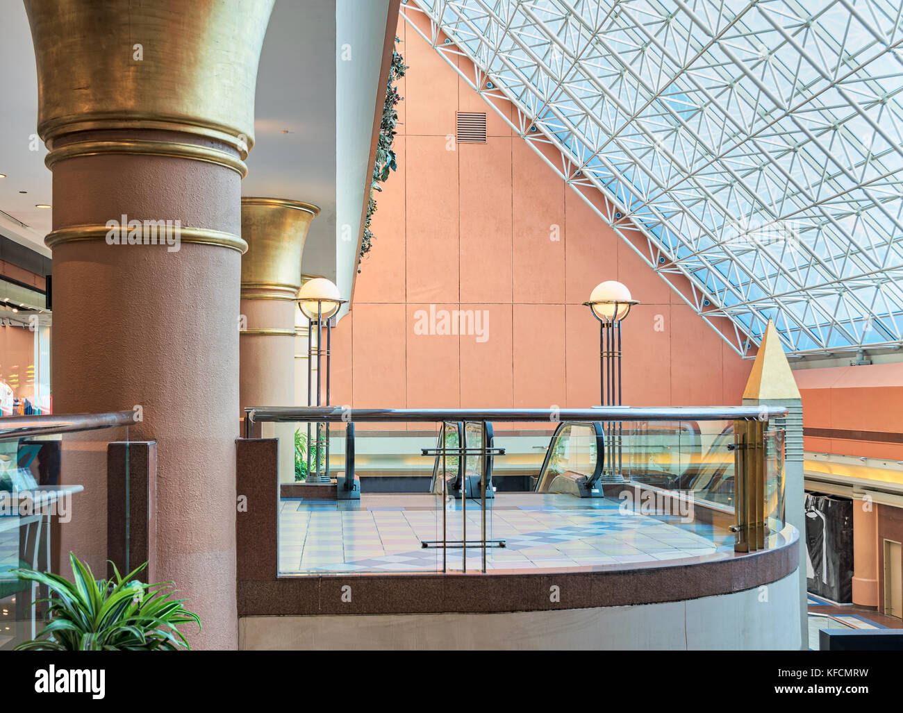 Modern shopping mall interior with glass balustrade transparent glass roof revealing blue sky - Stock Image