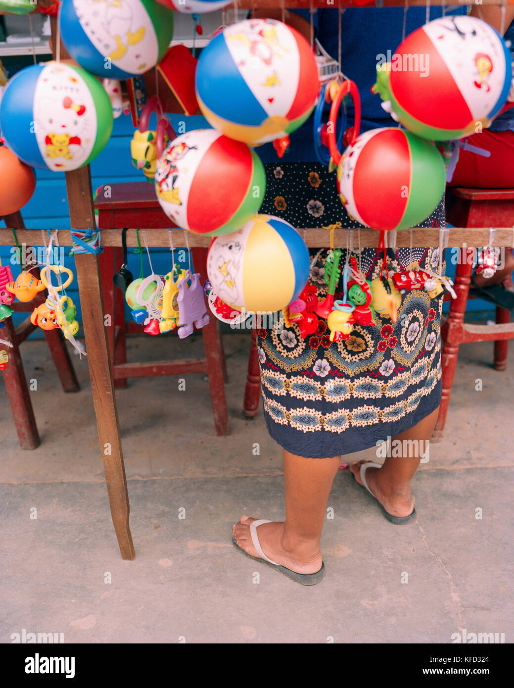 PERU, Amazon Rainforest, South America, Latin America, low section of a lady selling toys in market. - Stock Image