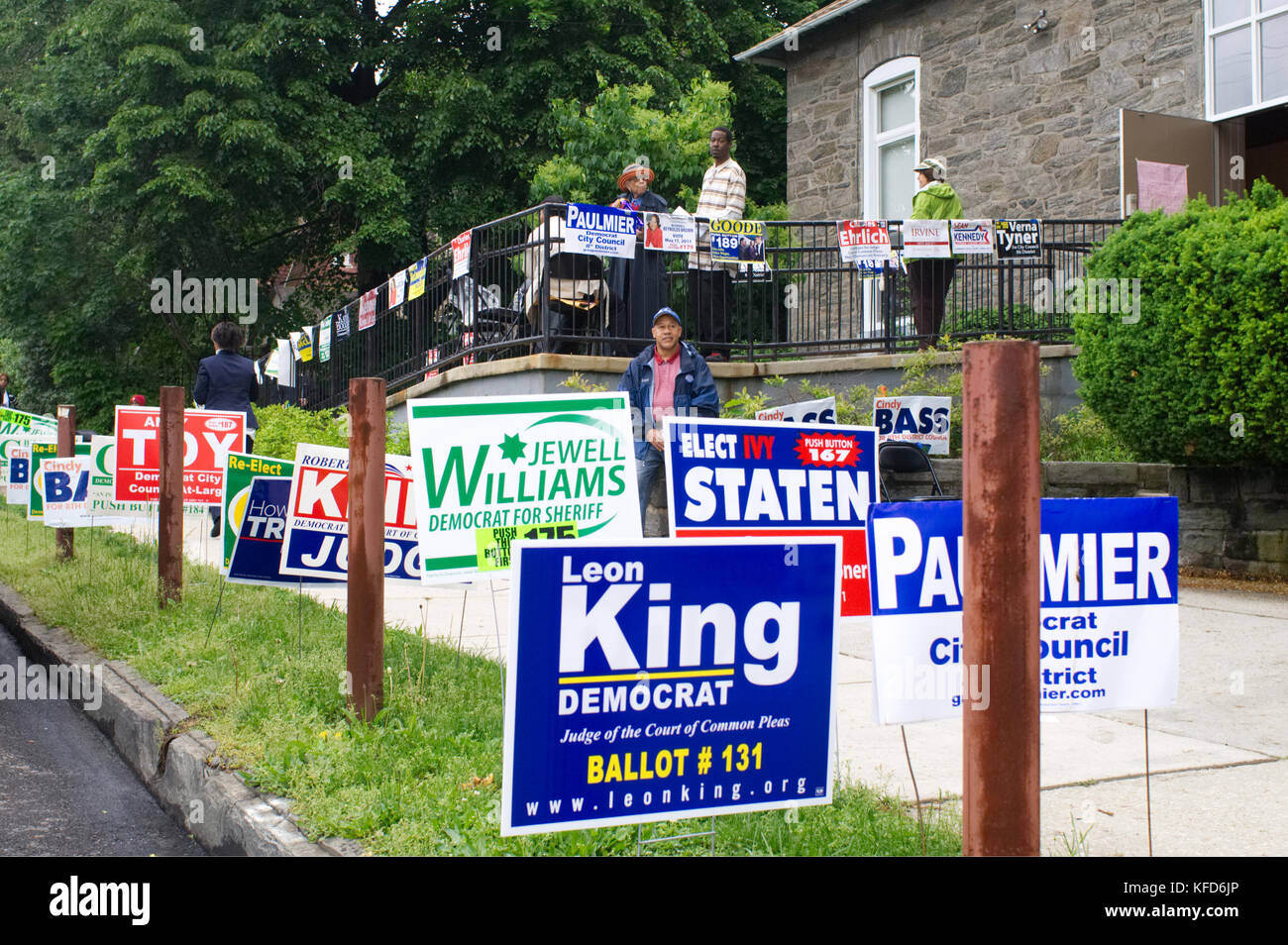 On Election Day numerous lawn signs are posted near the entrance of a polling station, as poll watchers and campaign - Stock Image
