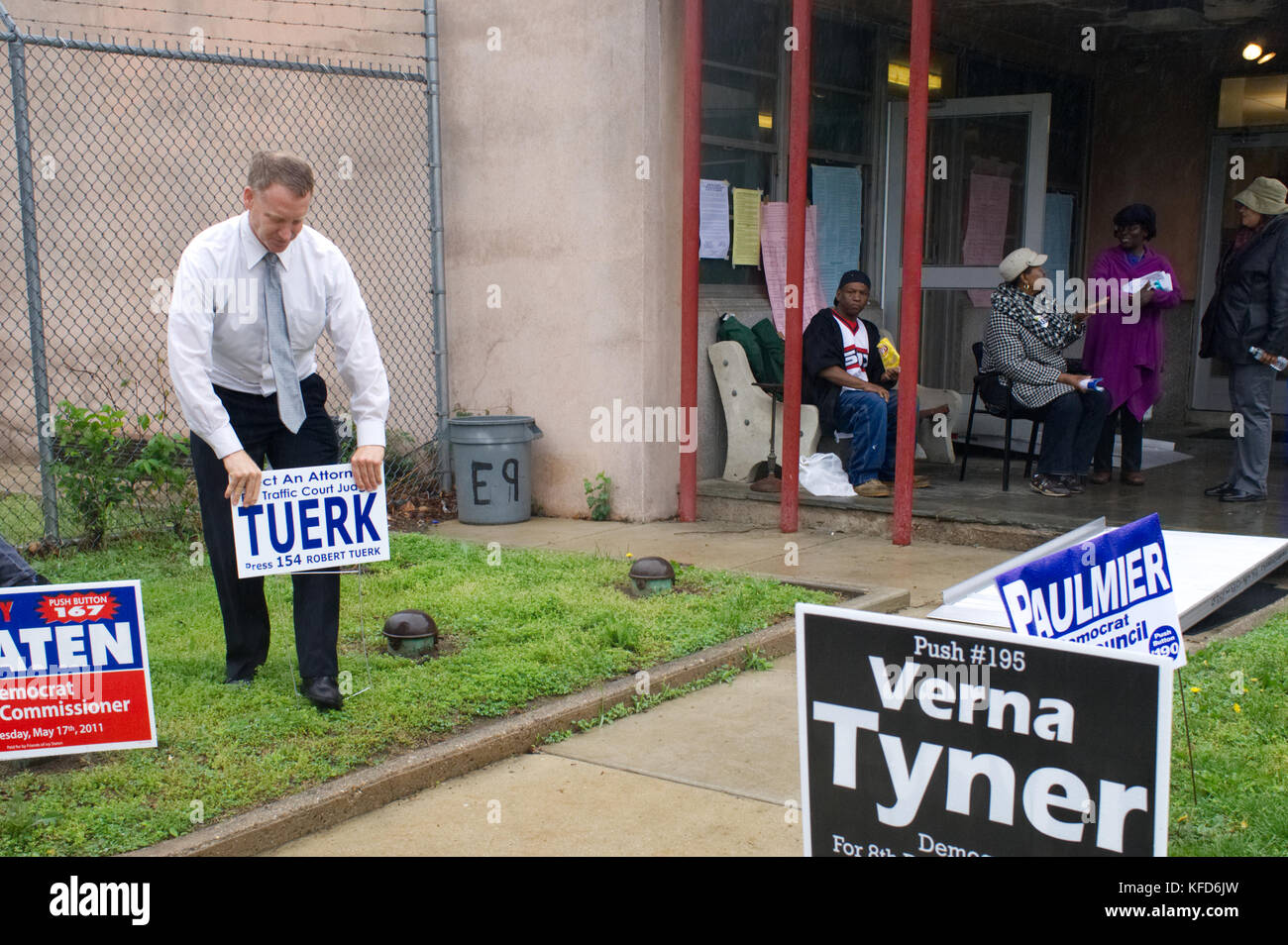 On Election Day a candidate running in local Primaries plants a lawn sing outside a polling station, in Philadelphia, - Stock Image