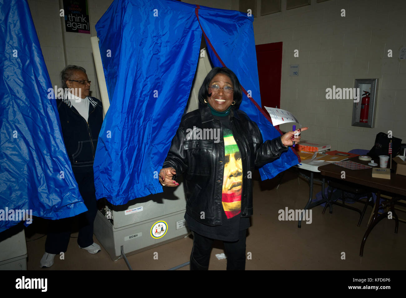 Voters emerge from behind the privacy curtain after casting the ballot inside an electronic voting machine, at a - Stock Image