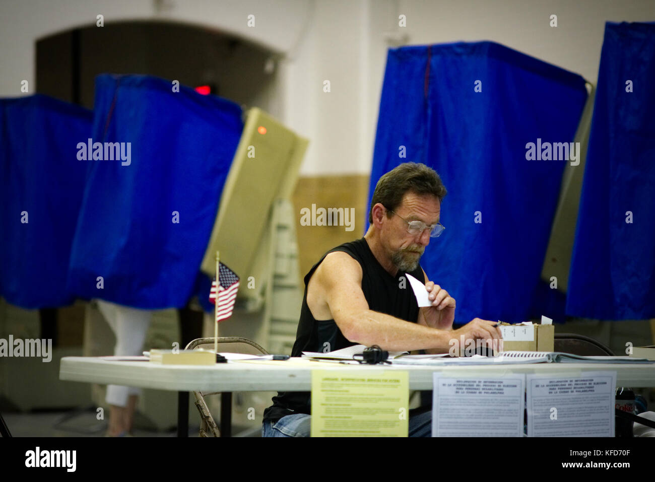 On Election Day a poll worker sits behind a table at a Philadelphia, PA polling station. - Stock Image