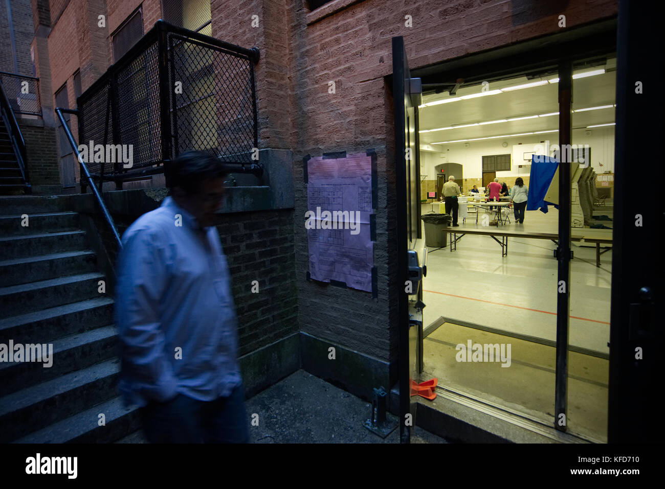 With minutes till polls close on Election Day a voter walks past open doors at a polling station, located in the - Stock Image