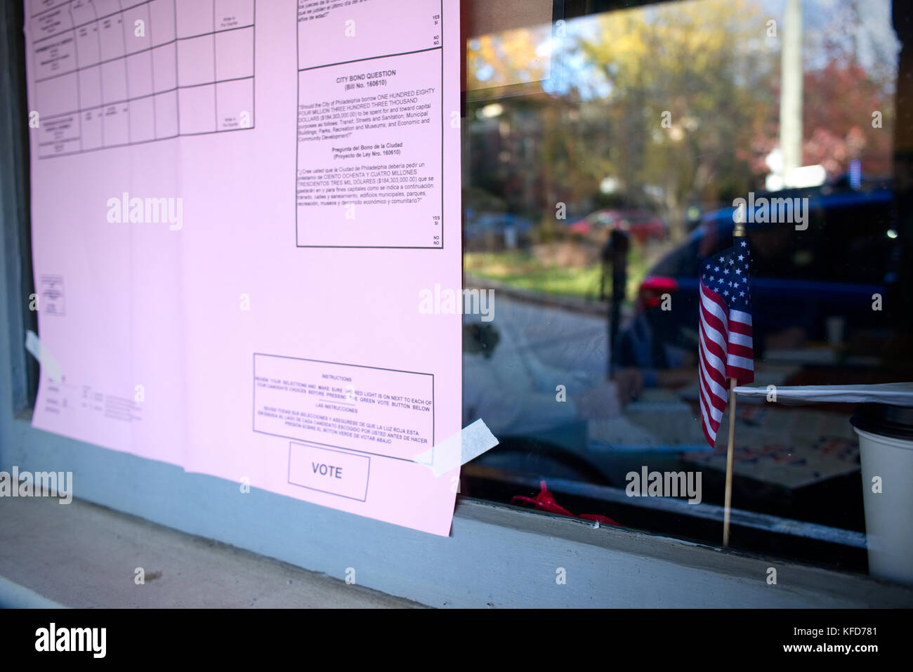 Small American flag sits behind a window of a polling station and an example ballot is posted on the outside, during - Stock Image