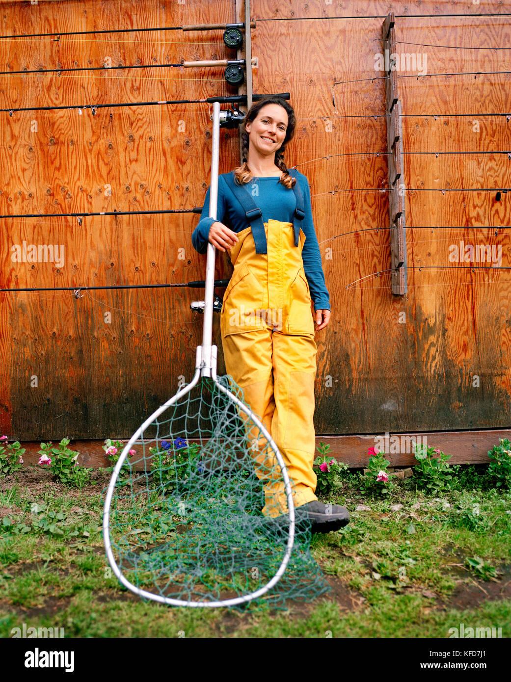 USA, Alaska, Redoubt Bay, a young woman fishing guide holds a fishing net, Redoubt Bay Lodge - Stock Image
