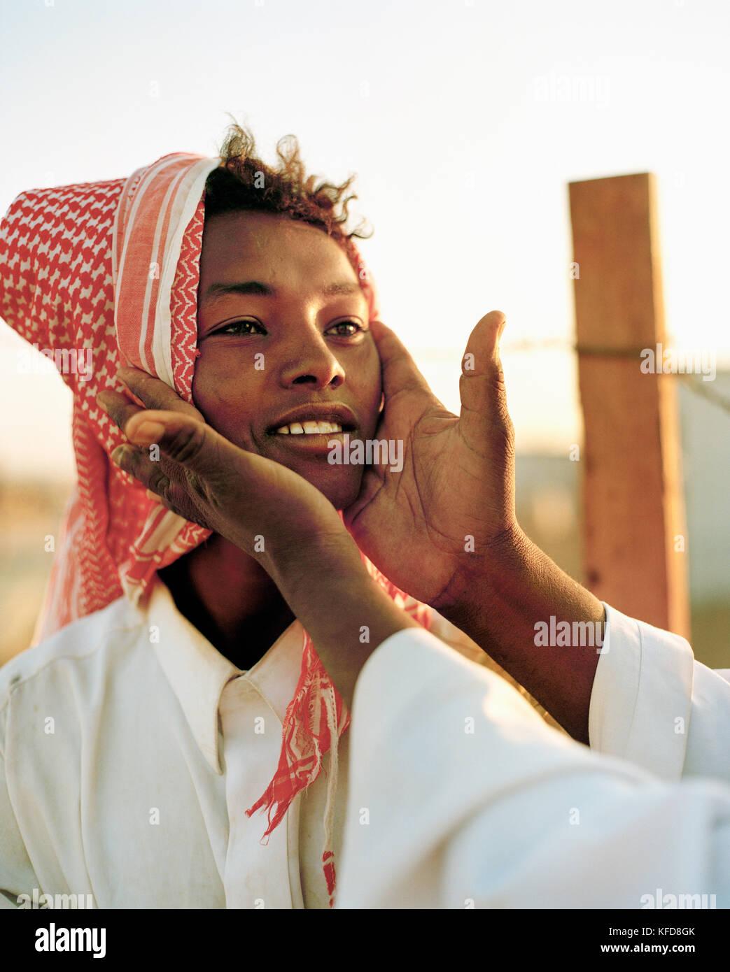 SAUDI ARABIA, Riyadh, a teenage boy works at a camel market in the desert outside of Riyadh - Stock Image