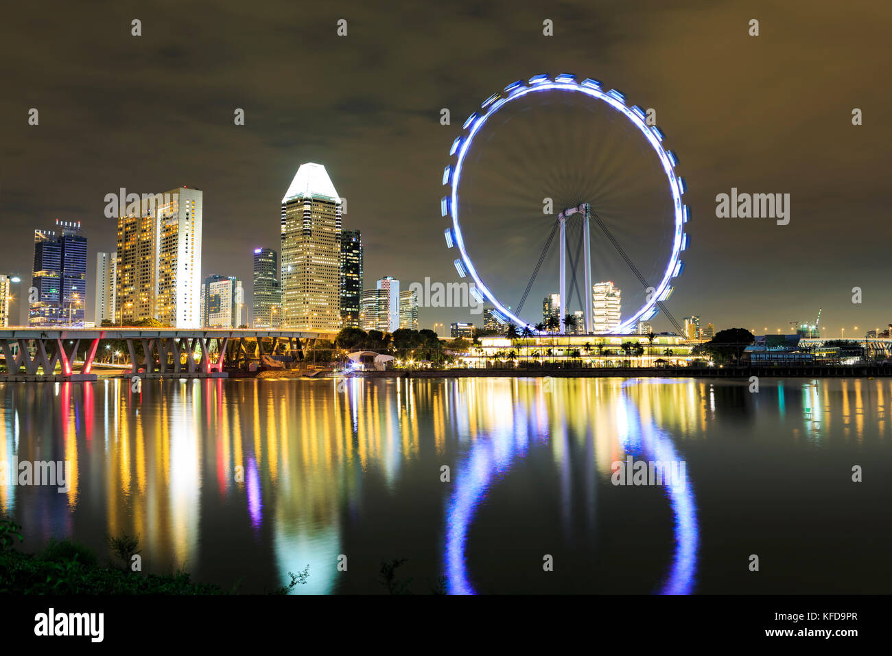 Marina Bay view with Singapur Flyer and skyline of Singapore town by night - Stock Image