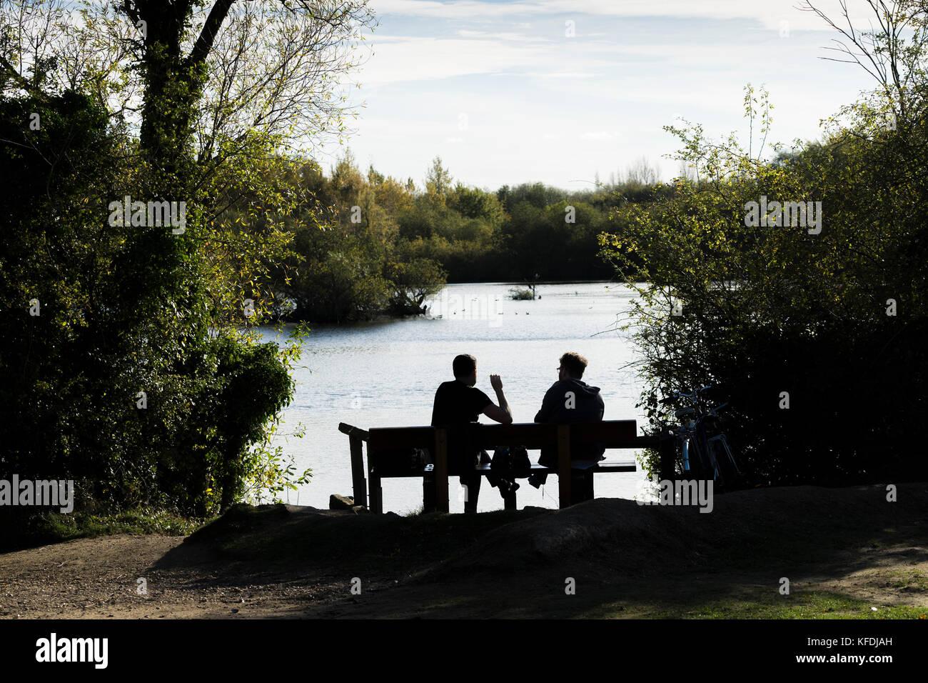 two-men-sat-by-lake-enjoying-warm-autumn