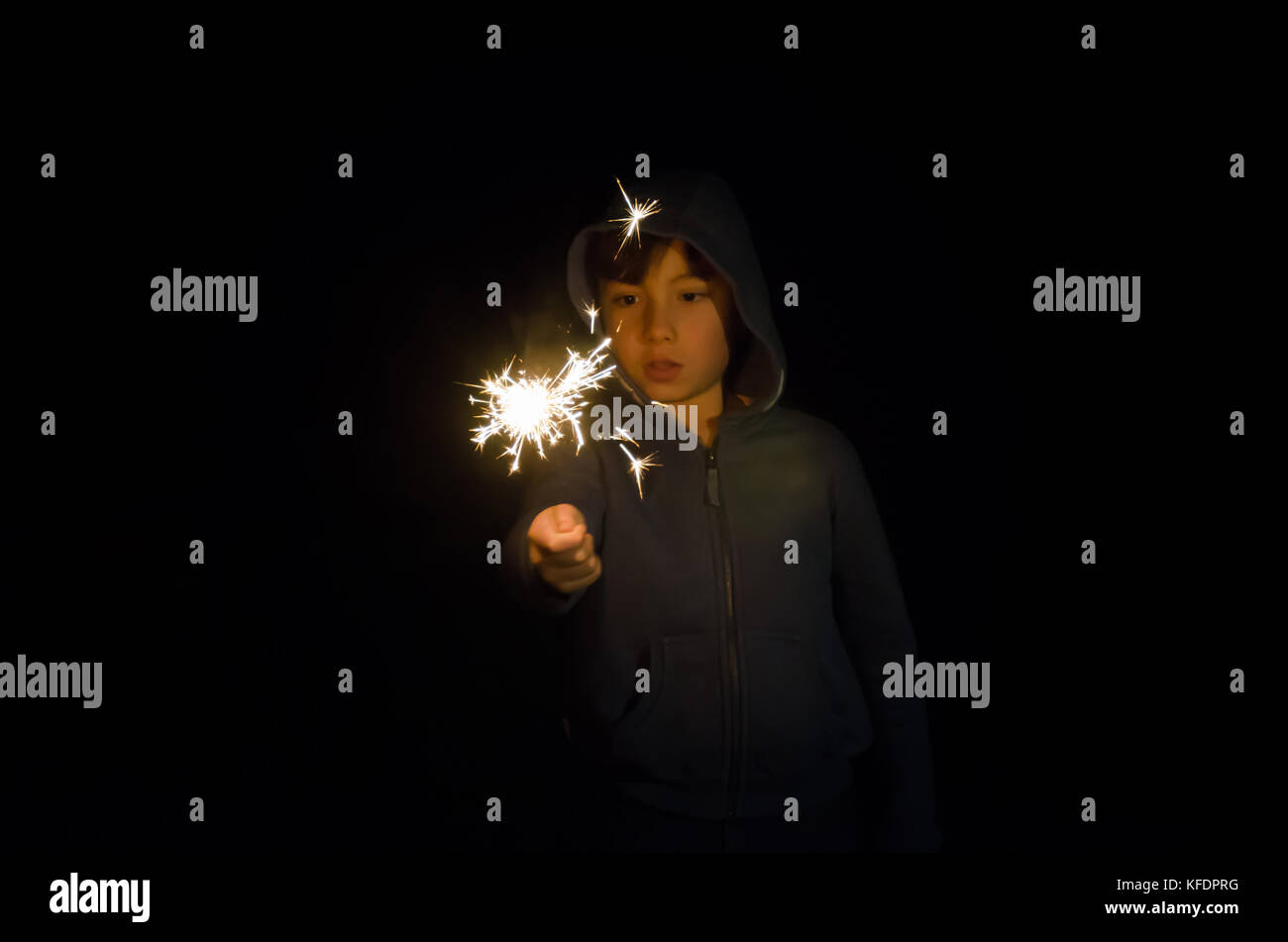 a-young-boy-playing-with-a-sparkler-in-the-back-garden-KFDPRG.jpg