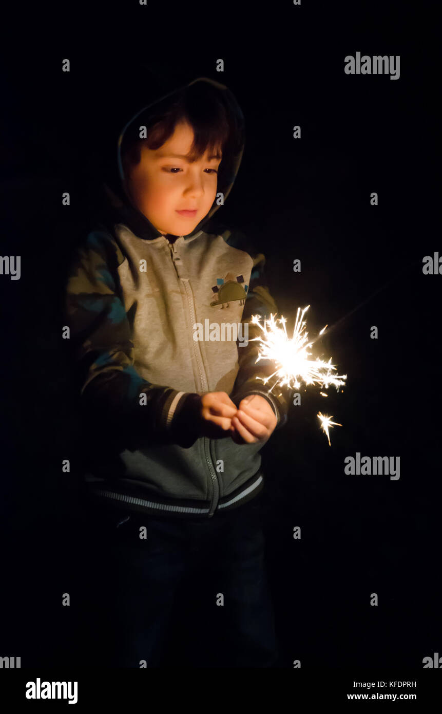 a-young-boy-playing-with-a-sparkler-in-the-back-garden-KFDPRH.jpg
