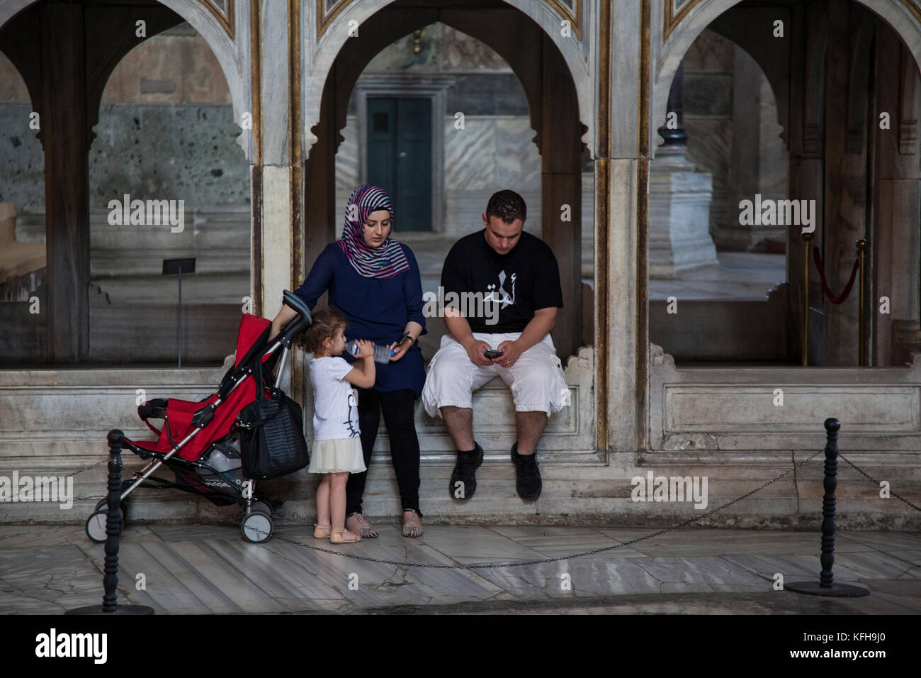 A moslem family takes a break while visiting the Apse Mosaic in the Hagia Sophia in Istanbul, Turkey. - Stock Image