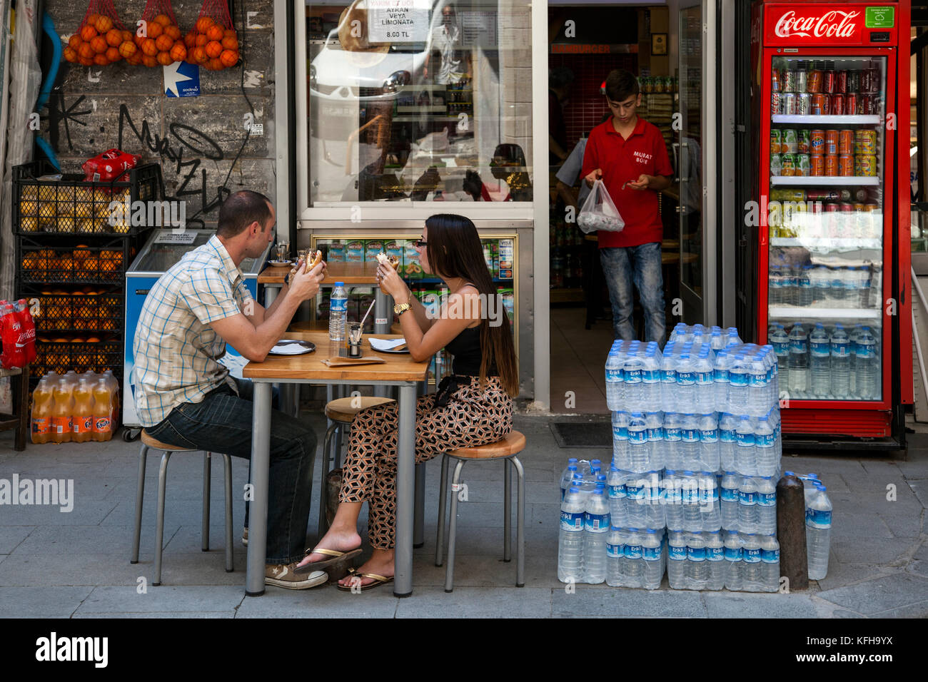 A couple eat lunch outside a market in Istanbul, Turkey, while another customer exits the store. - Stock Image