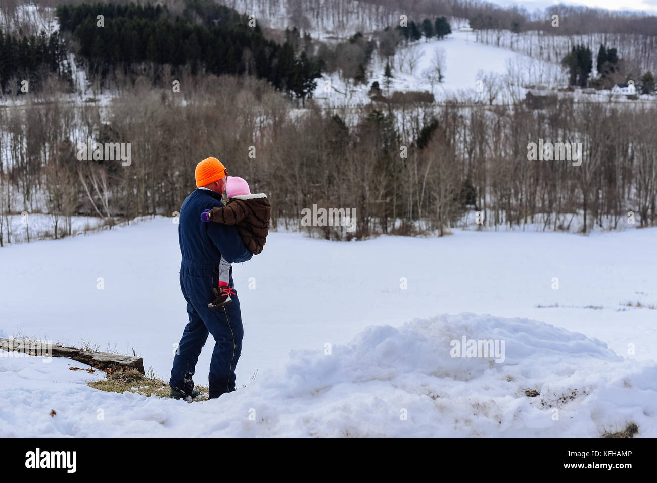 Man holding infant in winter with snow - Stock Image