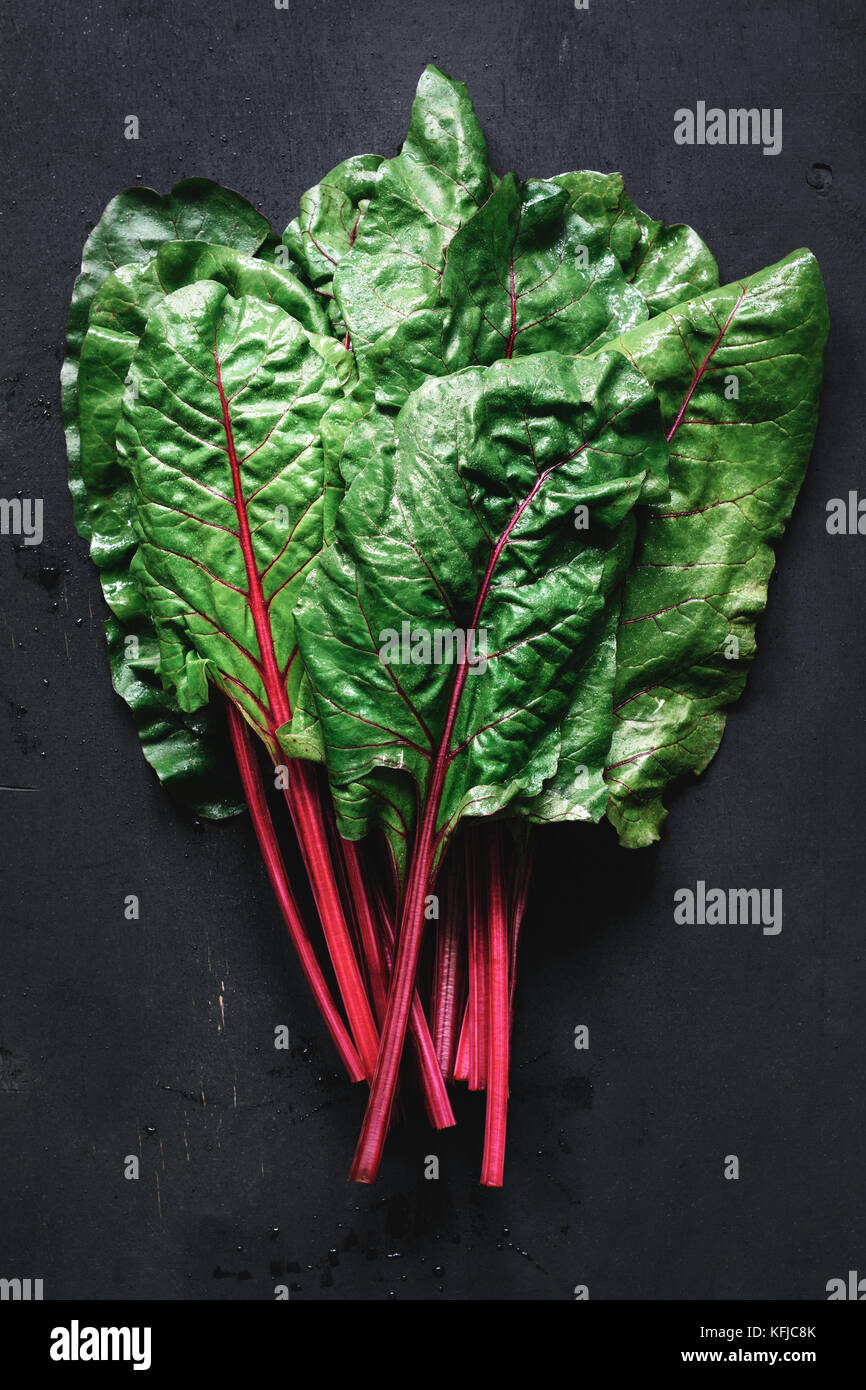 Fresh swiss chard leaves on black background. Table top view fresh organic green food - Stock Image