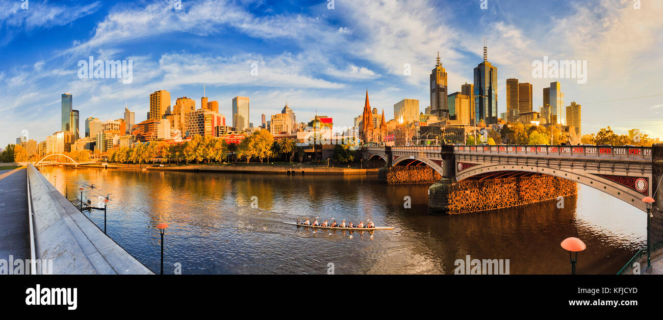Warm golden light over Melbourne city CBD across Yarra river from Southbank between Walk foot bridge and Princes - Stock Image