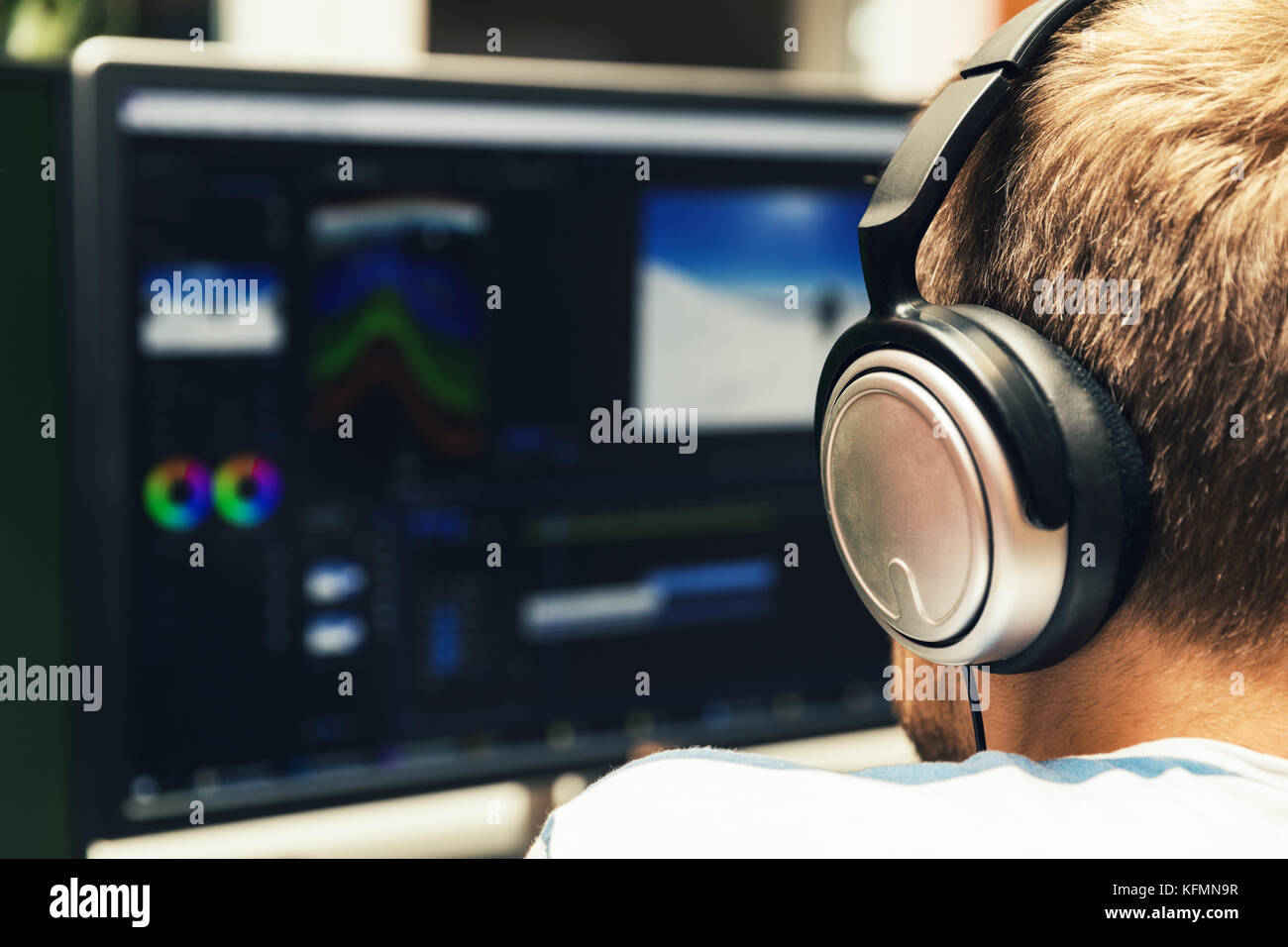 man doing video editing on computer with headphones on - Stock Image