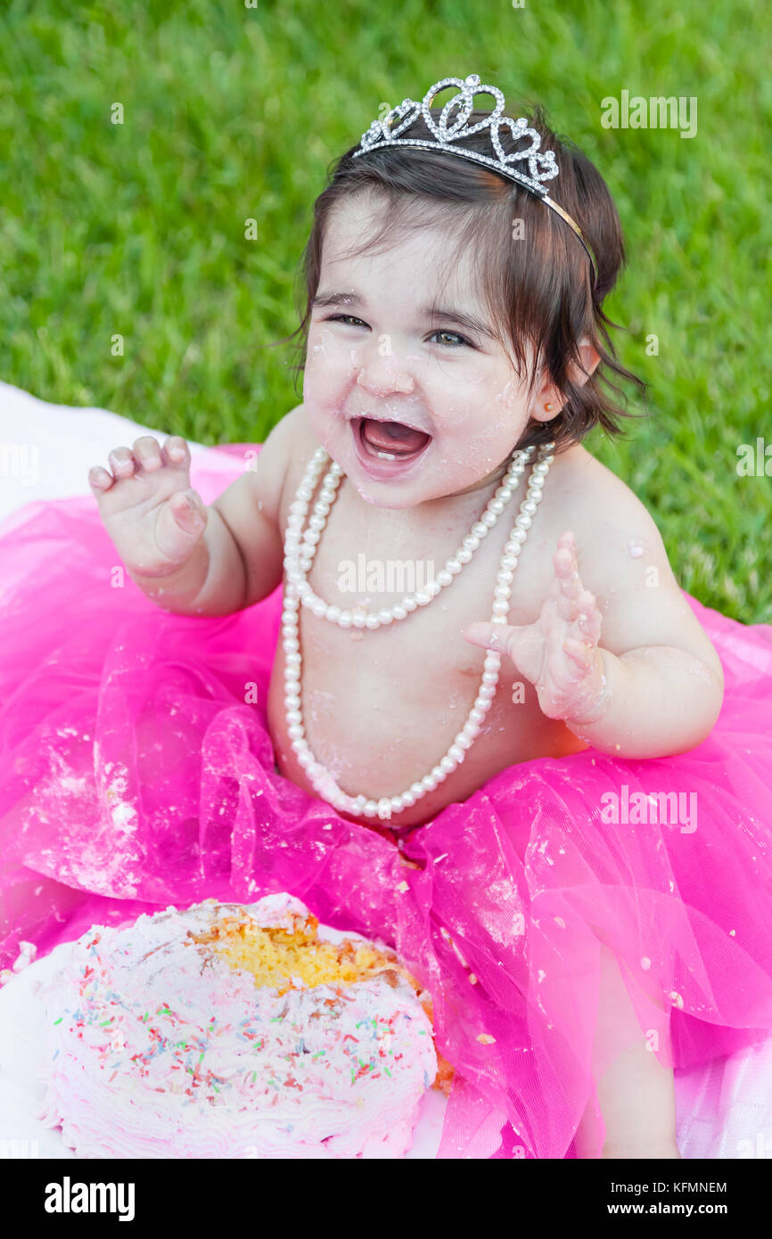 Smiling happy baby toddler girl first birthday anniversary party. Ecstatic and laughing, raised hands, face dirty - Stock Image