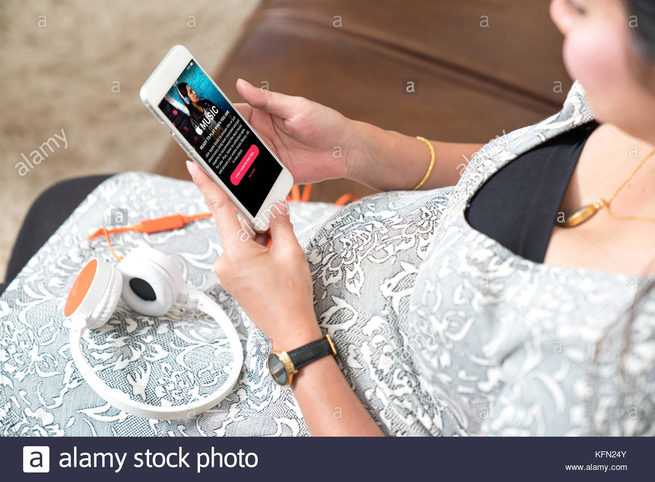 relax: Bangkok - December 12 2016: pregnant woman using an iPhone screenshot of Apple's Music app that shows - Stock Image