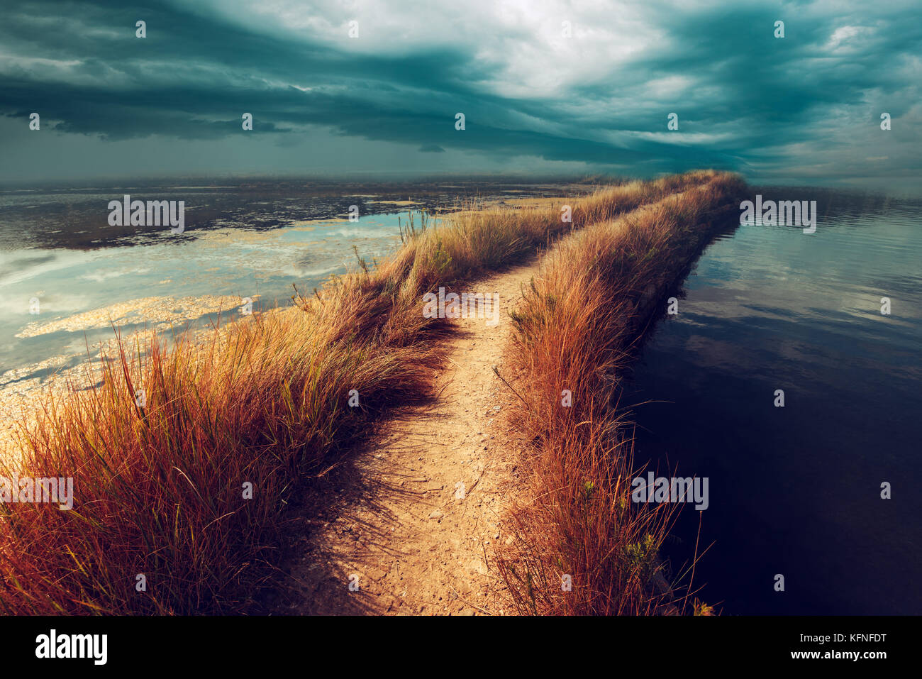 Uncertainty, doubt and insecurity in the future. Risky footpath road through water vanishing in distance dark stormy - Stock Image