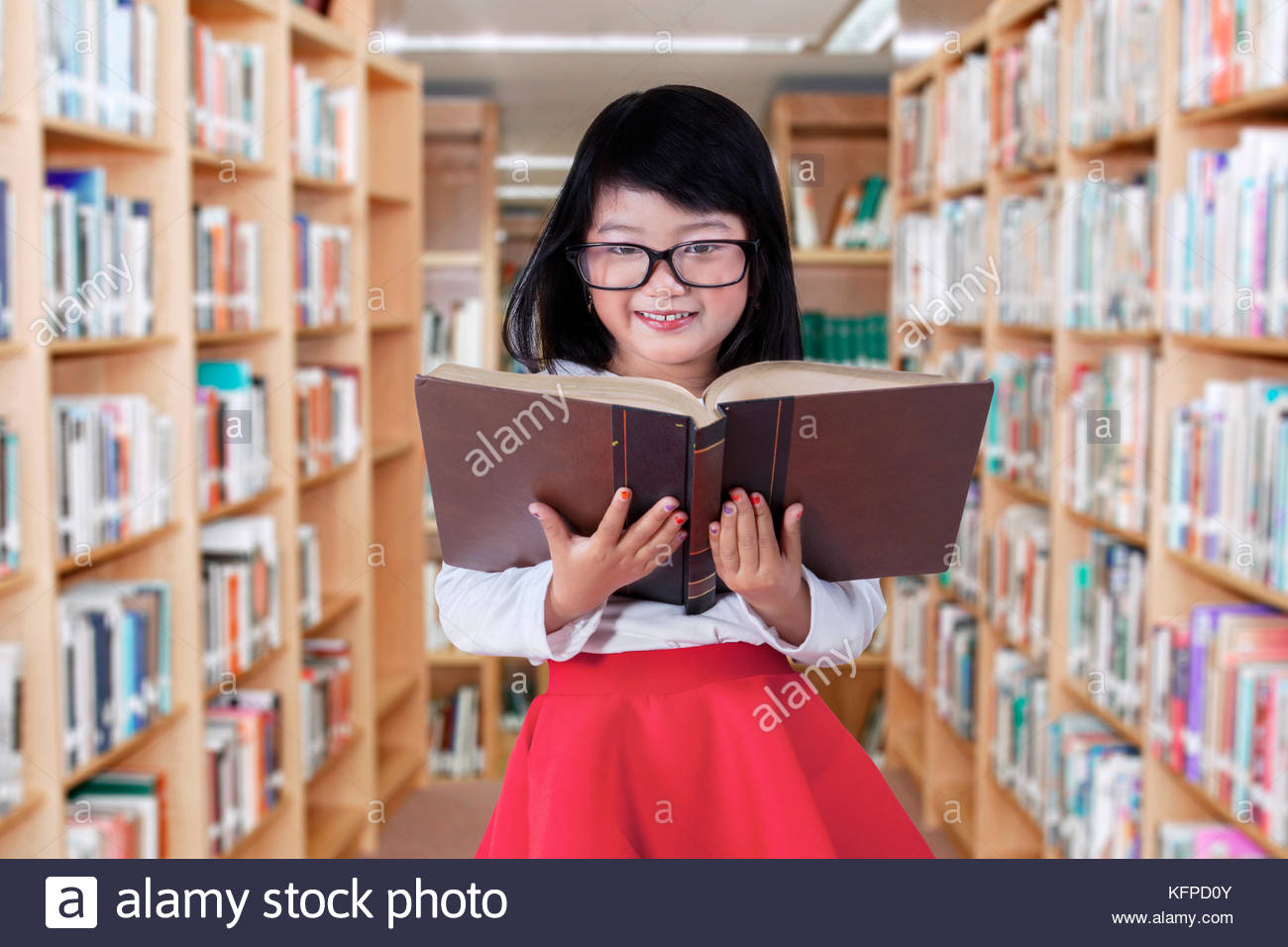 Lovely elementary school student standing in the library while reading a textbook - Stock Image