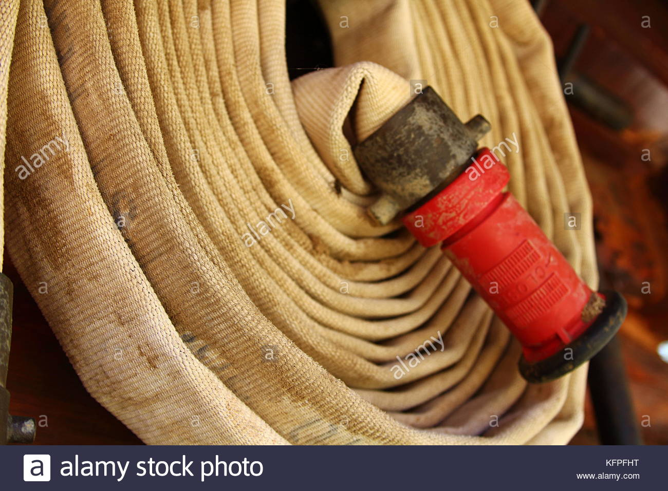 Rolled firehose ready for use - Stock Image