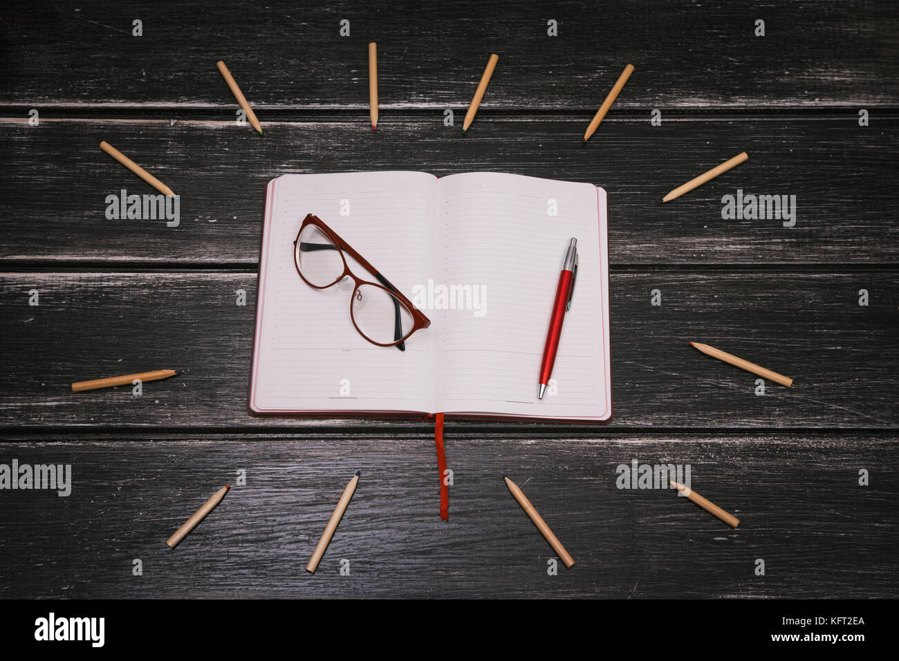 White notebook, pen and glasses and a lot of pencils on a black wooden background - Stock Image