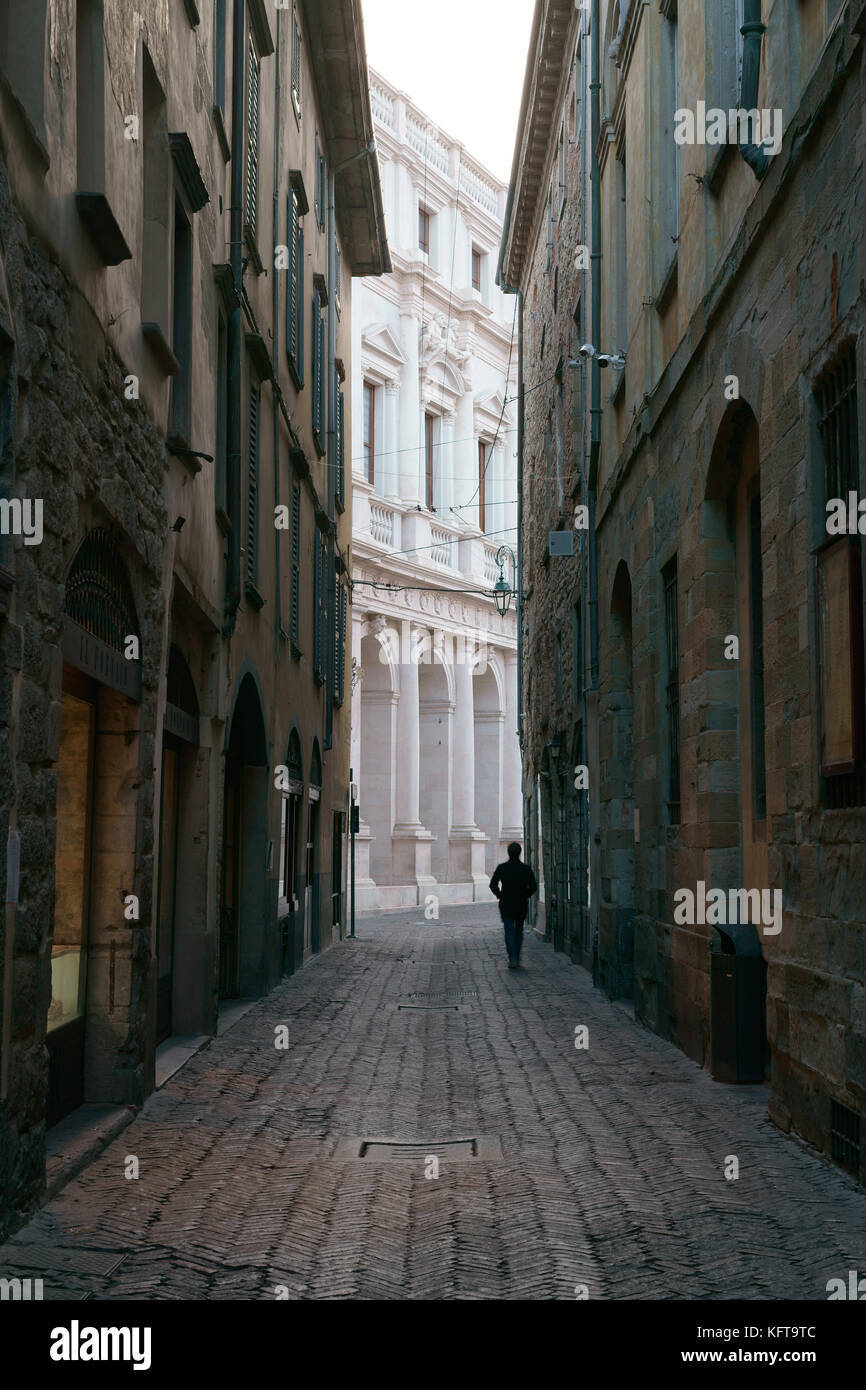 SILHOUETTE OF A MAN WALKING ON A DESERTED NARROW STREET. Città Alta (Upper City), Bergamo, Lombardy, Italy. - Stock Image
