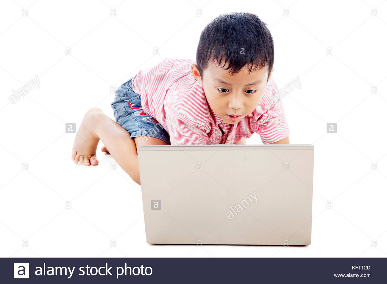 Cute asian boy using laptop computer seriously. shot in studio - Stock Image