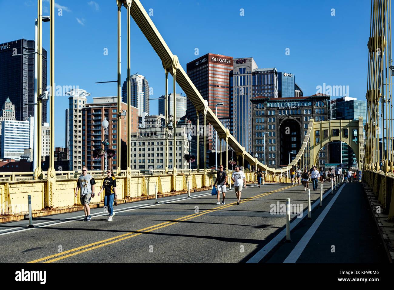 People walking across Roberto Clemente Bridge and skyline, Pittsburgh, Pennsylvania USA - Stock Image