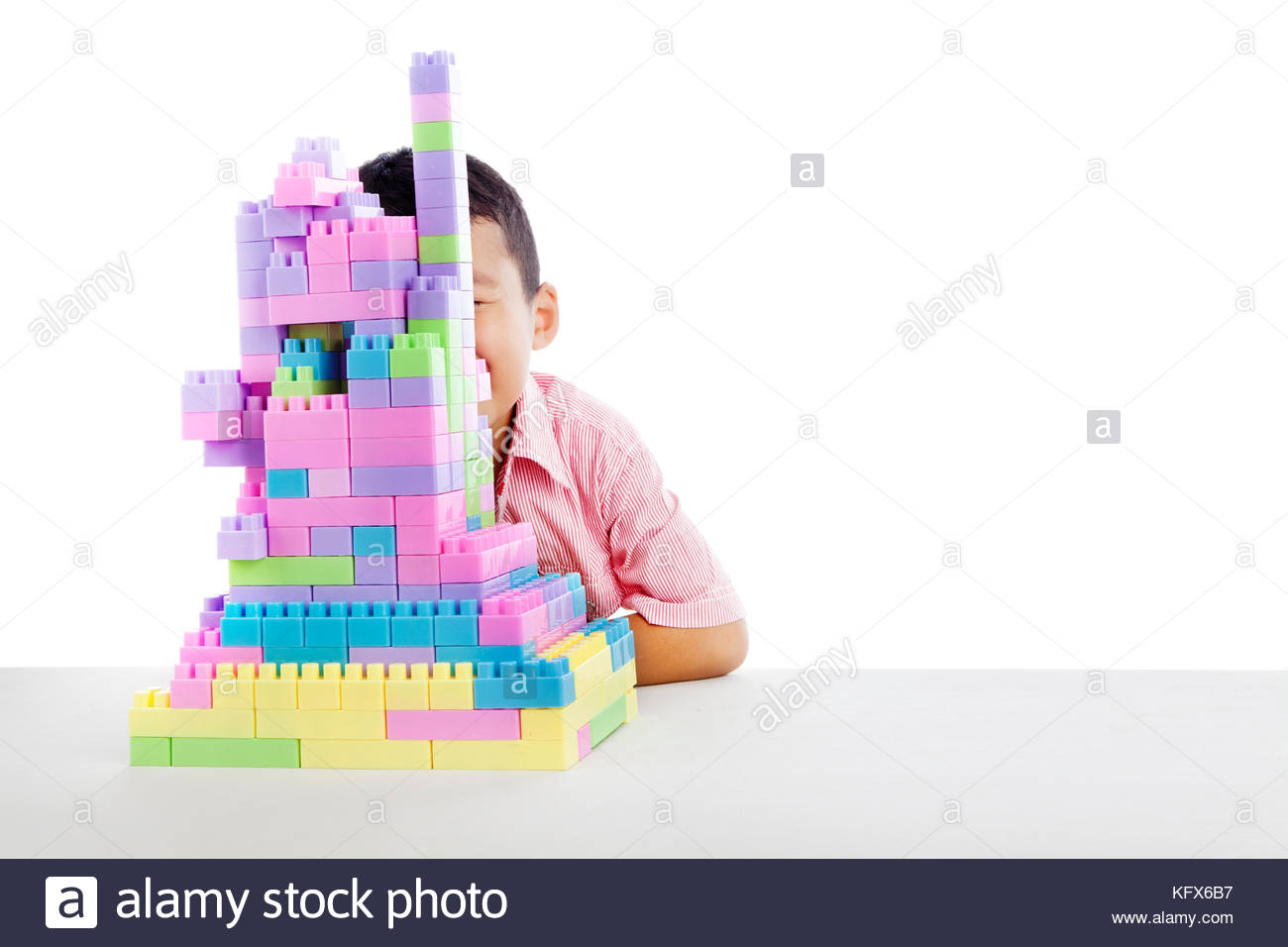 Boy hiding his face behind  blocks shot in studio isolated on white - Stock Image