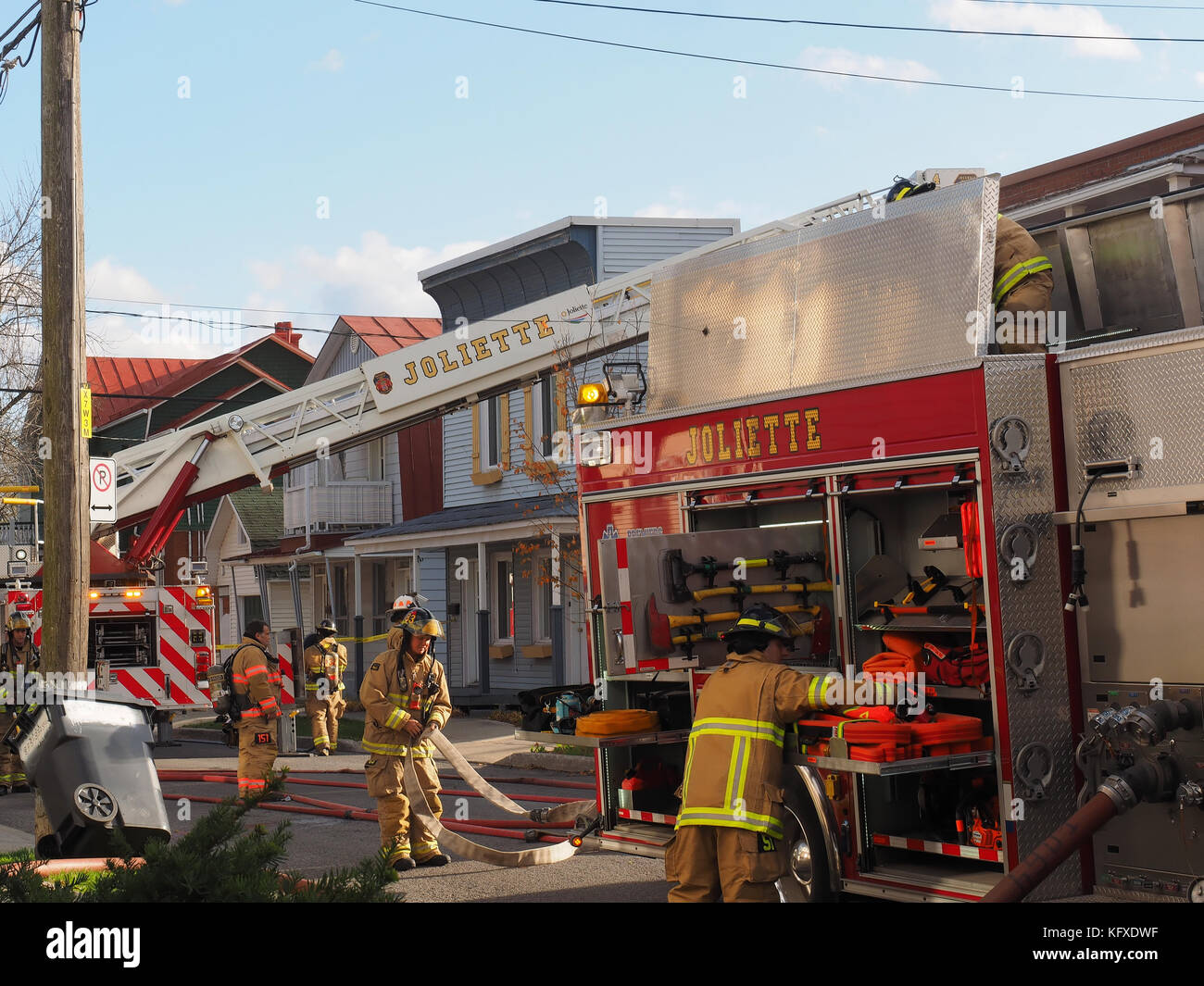 Firemen rolling up their hoses at the scene of a building fire in Joliette, Quebec, canada - Stock Image