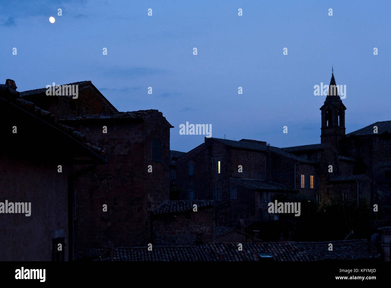 The moon rises over the Medieval Quarter in the Umbrian town of Orvieto, Italy. - Stock Image